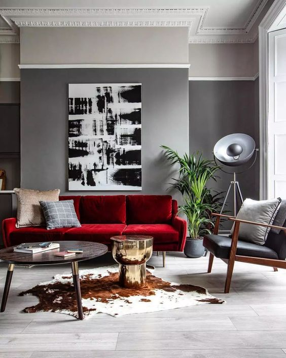 a modern living room with grey walls, a bold red sofa, a black leather chair, a monochromatic artwork and a round table