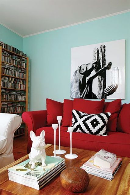 a modern living room with turquoise walls, a bold red sofa, a bookcase, a monochromatic artwork and a low table with decor