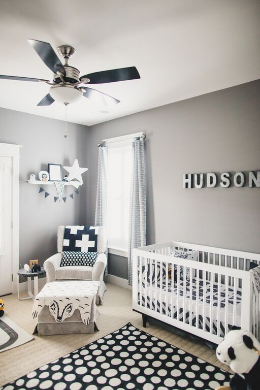 a modern monochromatic nursery with grey walls, white furniture, printed textiles, a name on the wall and pretty decor