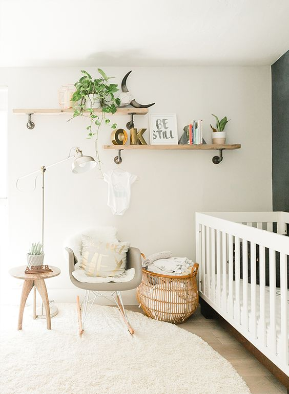 a modern neutral nursery with a grey accent wall, a large white crib, a grey chair, a basket and some wooden shelves