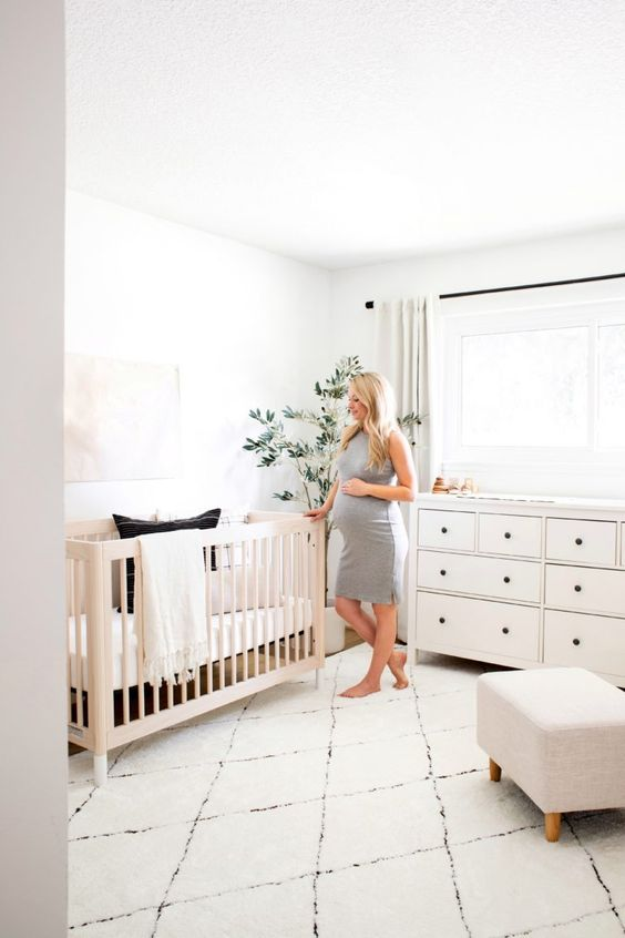 a modern neutral nursery with a light stained crib, a white dresser and a neutral ottoman plus neutral textiles