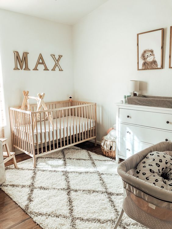 a modern neutral nursery with a stained crib, a white dresser, a printed rug, a letter art and some other artworks