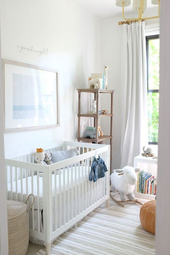 a modern neutral nursery with a white crib, some storage units, a leather pouf, some toys and a chic chandelier