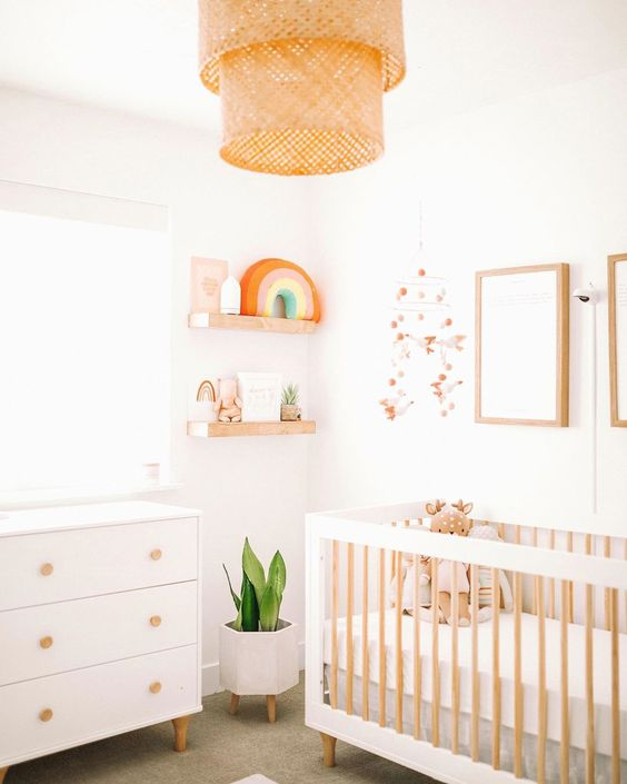 a modern neutral nursery with a white dresser and a large crib, a woven lamp and shelves with pretty decor