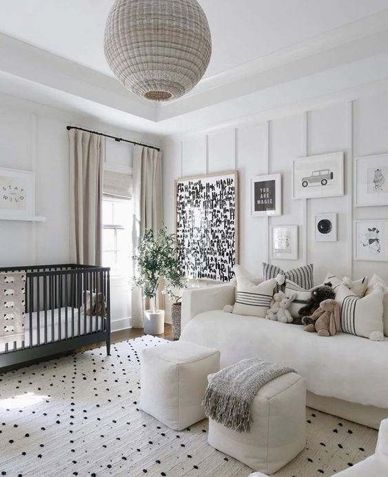 a modern neutral nursery with paneled walls, a black crib, neutral furniture, a gallery wall, printed textiles and a rattan pendant lamp