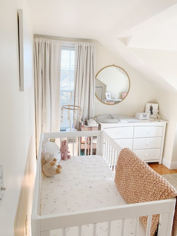 a modern neutral nursery with white furniture, printed and pastel bedding, grey curtains, a round mirror and pretty toys