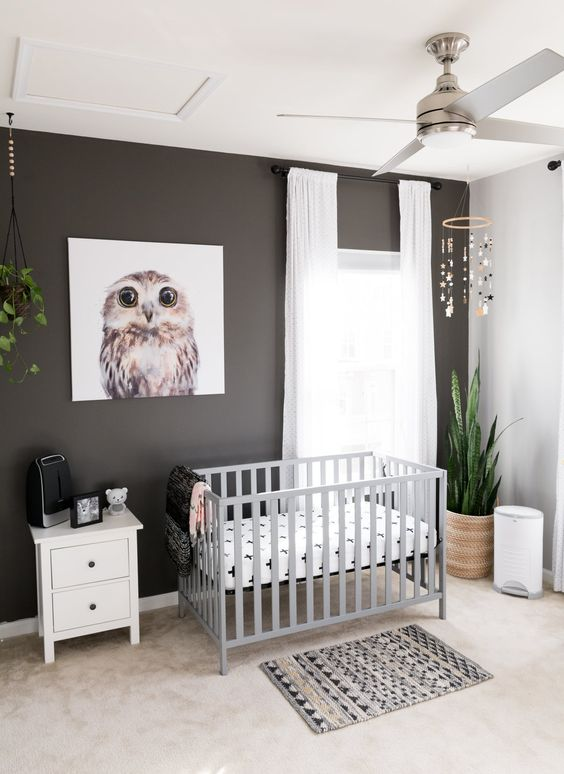 a modern nursery with a black accent wall, a grey crib, potted plants, a printed rug and neutral curtains is very cool