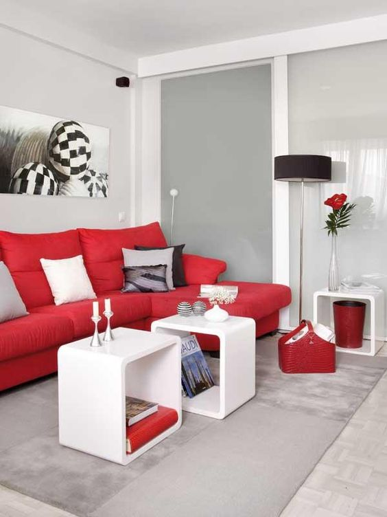 a monochromatic contemporary living room in white and light grey, with a bold red sofa and other touches for a brighter look