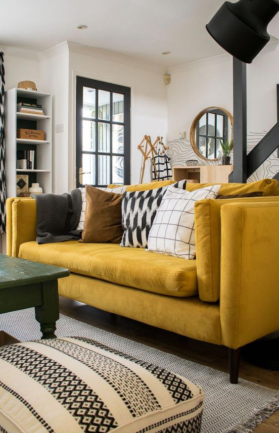 a monochromatic living room with graphic prints, a bold yellow sofa, a green table and a cool shelving unit
