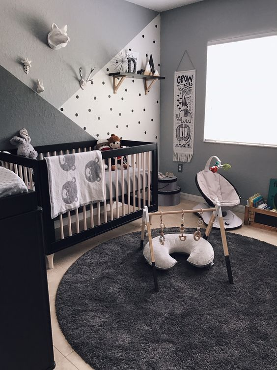a monochromatic zoo inspired nursery with a cool crib, a black dresser, lovely kid's facilities, an accent wall and animal plush toys