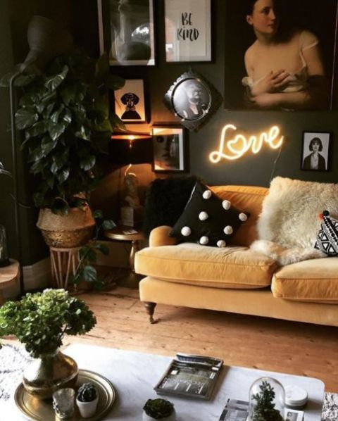 a moody living room with a black and white gallery wall, a pale yellow sofa for a touch of color and potted plants