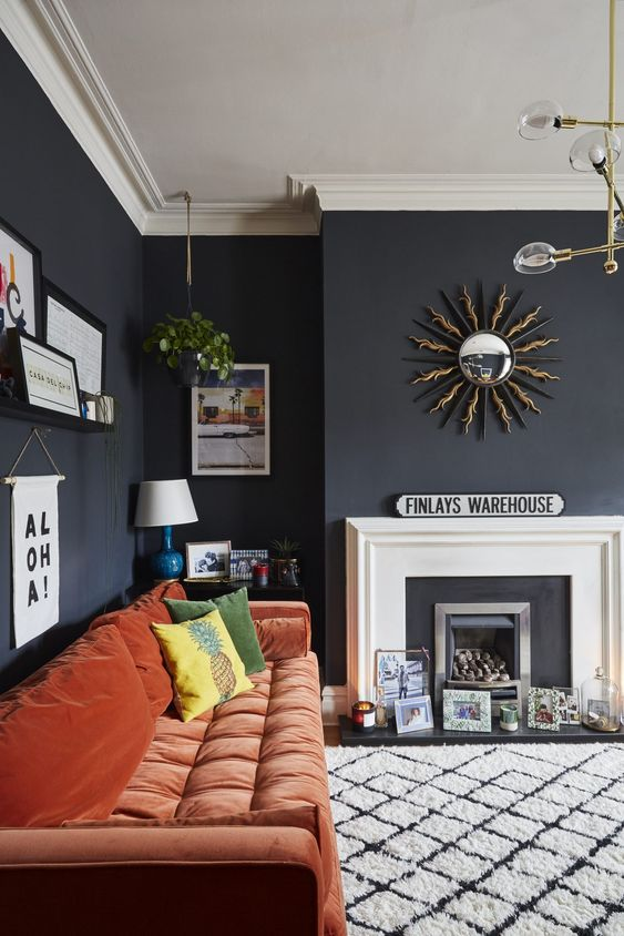 a moody living room with a faux fireplace, artworks, prints and candles, a rust colored sofa and a pretty gallery wall
