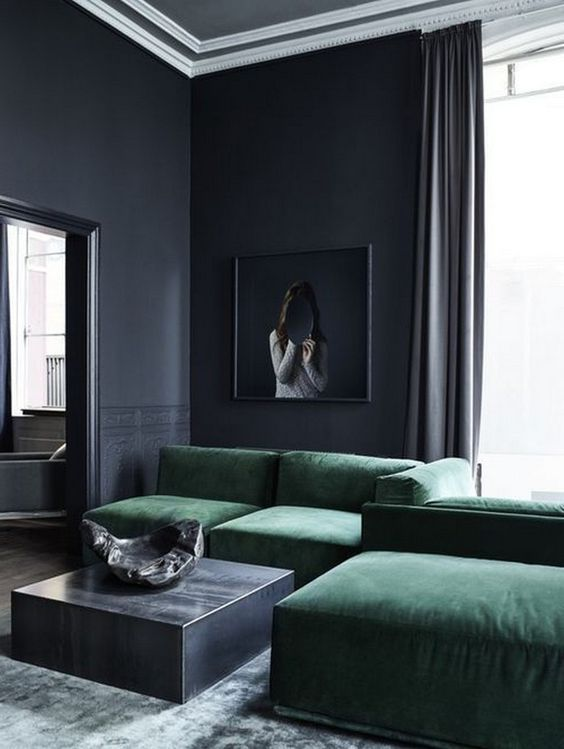 a moody living room with black walls, a low emerald sofa, a low metal coffee table and a statement artwork