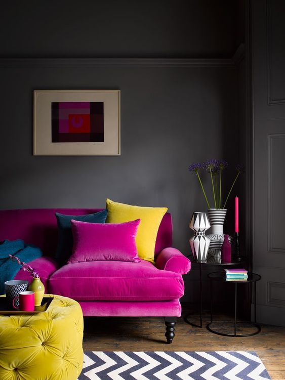 a moody living room with grey walls, a hot pink sofa, a yellow tufted ottoman, a printed rug, chic vases and candles