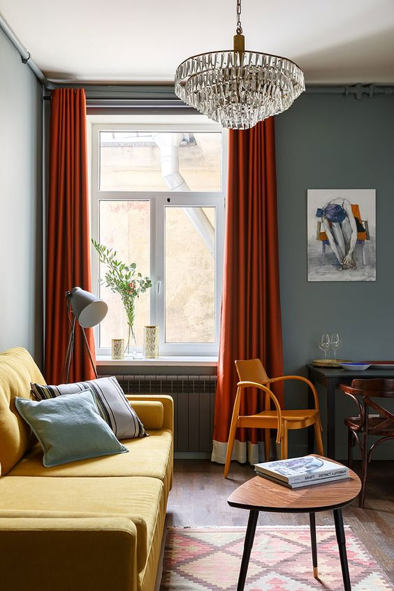 a moody living room with grey walls, a yellow sofa, rust-colored curtains, a crystal chandelier and vintage chairs and tables