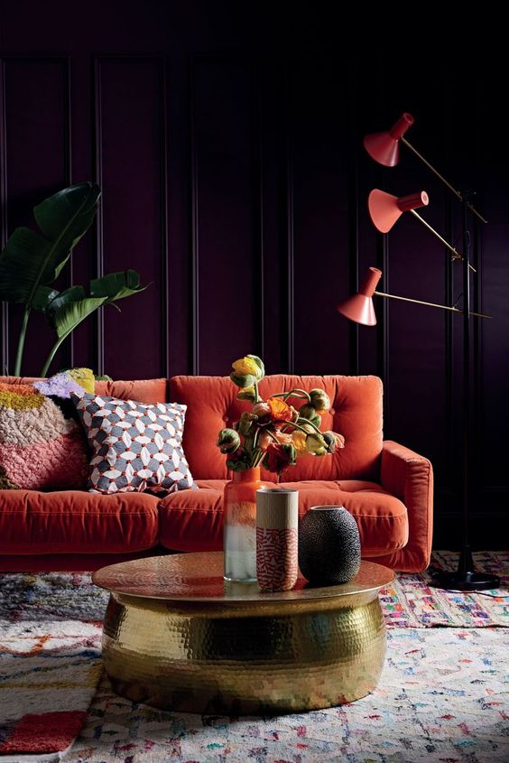 a moody living room with purple paneled walls, an orange sofa, orange floor lamps, a gold hammered table and statement plants
