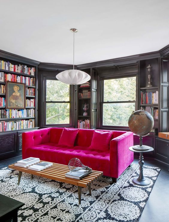 a moody room with a bay window, built-in bookshelves, a hot pink tufted sofa for a color accent in the space