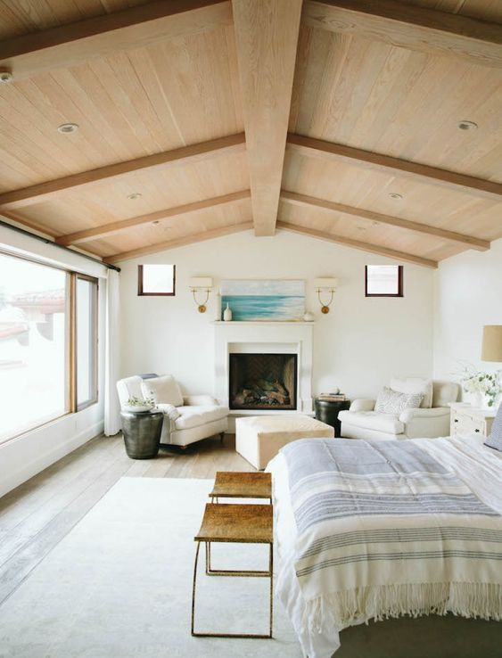a neutral and beautiful bedroom with a panoramic window, a blonde wood ceiling with beams, a fireplace, white chairs and an ottoman, a bed and leather stools