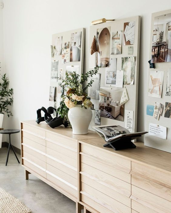 a neutral and welcoming space with large blonde wood sideboards, meom boards over them and potted plants and blooms