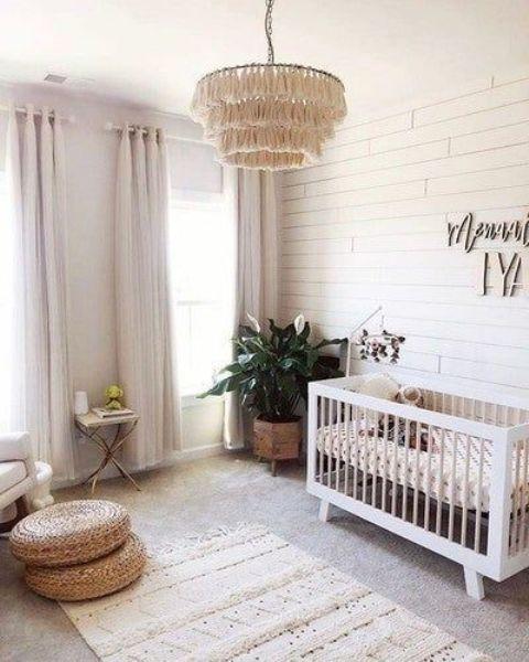 a neutral boho nursery with a white crib, a chair and a small table, jute cushions, a boho rug and a tassel chandelier