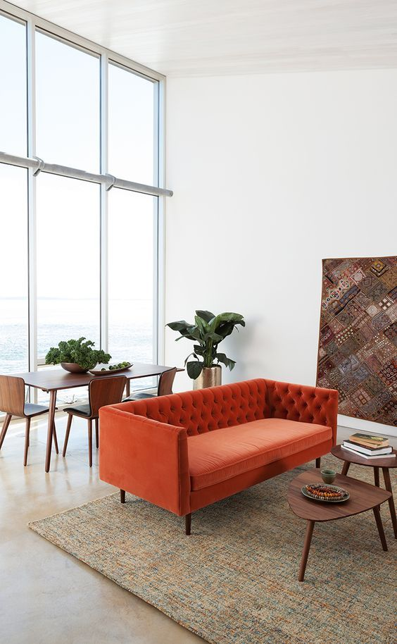 a neutral double height ceiling space, with an orange sofa, a duo of tables and a dining zone by the window