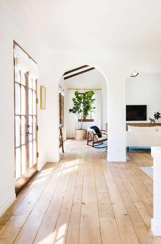 a neutral farmhouse entryway with blonde wood floors, French doors and neutral furniture is chic and cool