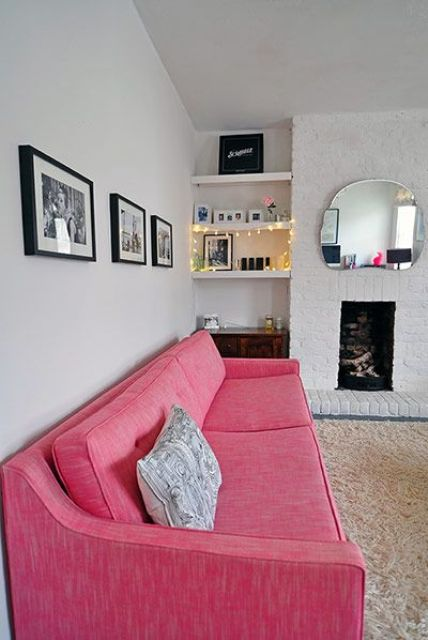 a neutral living room with a non-working fireplace, built-in shelves, a pink sofa for a touch of bold color and a grid gallery wall