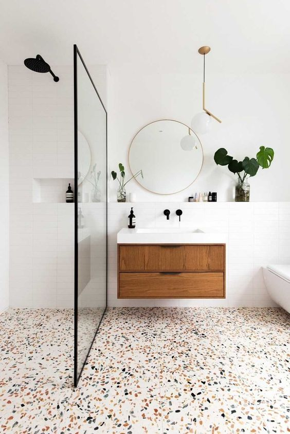 a neutral mid century modern bathroom done in neutrals, with white skinny tiles, a terrazzo floor and with black and brass fixtures and touches
