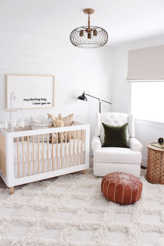 a neutral nursery with a cool crib, a white chair, a green pillow and a brown leather pouf plus pillows and toys