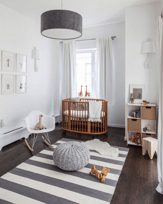 a neutral nursery with a stained crib, a white chair and a stool, a storage unit, a striped rug, a pendant lamp and a pouf