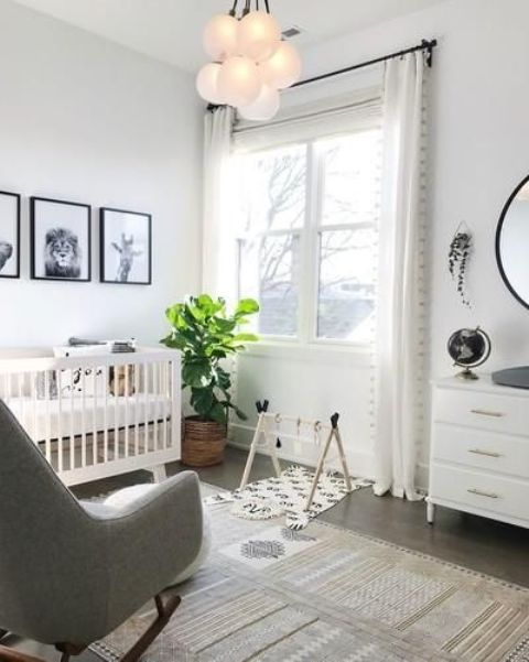 a neutral nursery with a white crib, a grey rocker, a white dresser, a statement plant and a gallery wall with black and white art