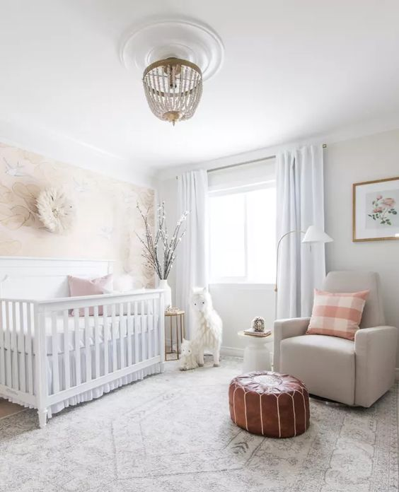 a neutral nursery with neutral furniture, a leather pouf, a beaded chandelier and printed pillows