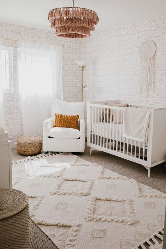 a neutral nursery with white furniture, a basket for storage, a tassel chandelier, a jute pouf, boho rugs