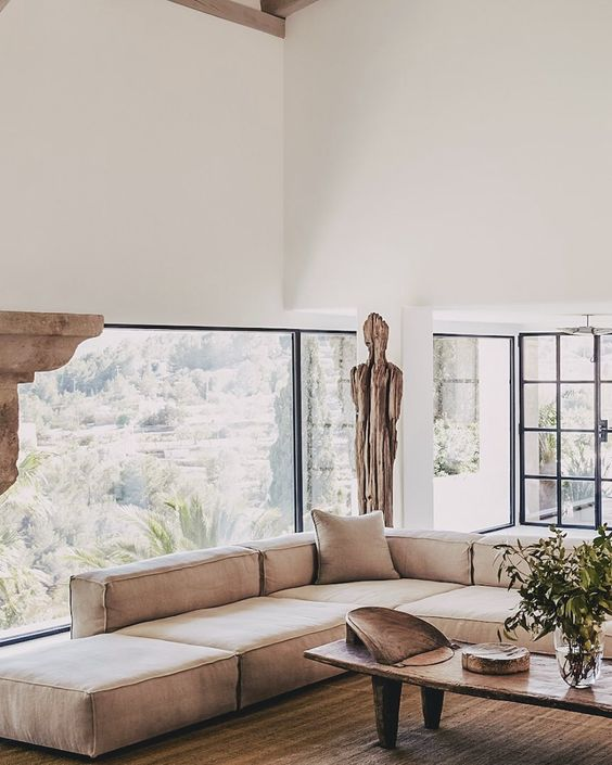 a neutral serene living room with a glazed wall, a low tan sofa, touches of wood, a wabi sabi low coffee table and greenery