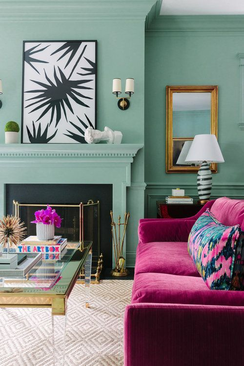 a pastel green living room with a non-working fireplace, lovely artworks, a fuchsia sofa with florla pillows and a lovely table