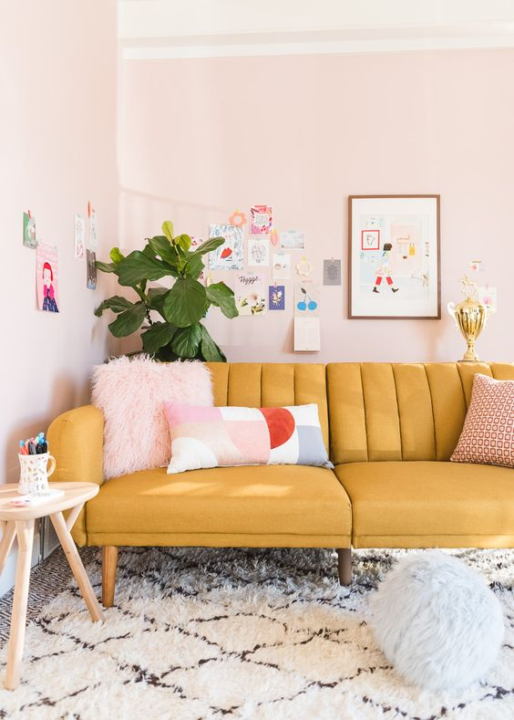 a pastel living room with a yellow sofa, blush walls, a colorful and fun gallery wall and a potted plant