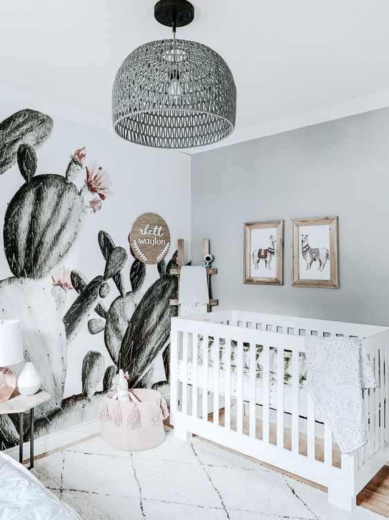 a playful neutral nursery with a grey wall, a white crib, a printed rug and a gorgeous cactus wall mural plus a pendant lamp