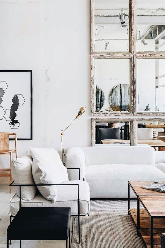 a pretty living room with a white low sofa, a low wooden table, a black stool, a mirror framed wall and a cool artwork
