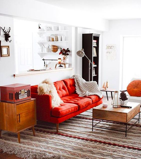 a pretty mid-century modern living room done in neutrals and spruced up with bold touches – a red sofa, a chest and an orange pillow