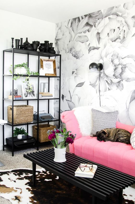 a pretty monochromatic living room with a floral wall, a storage unit, a black table and a bright pink sofa with printed pillows