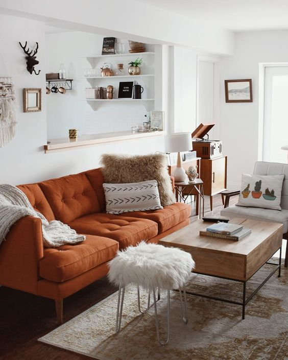 a pretty neutral living room in boho style, with a rust colored sofa, a low table and a fur stool, printed textiles is very welcoming