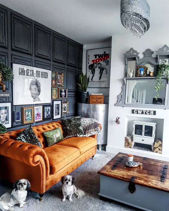 a quirky living room with a black paneled wall, an orange sofa, a mini hearth and a mirror, a whimsy gallery wall and a low table