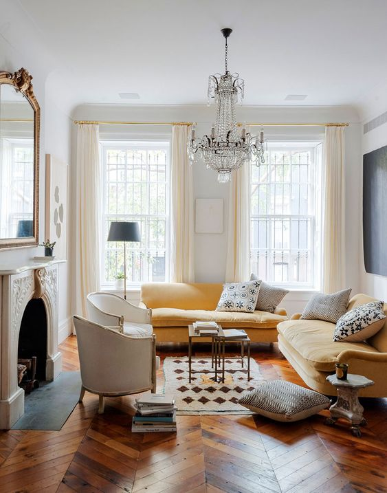 a refined Parisian living room with a non working fireplace, a yellow sectional, a refined crystal chandelier, creamy chairs and a large mirror over the fireplace