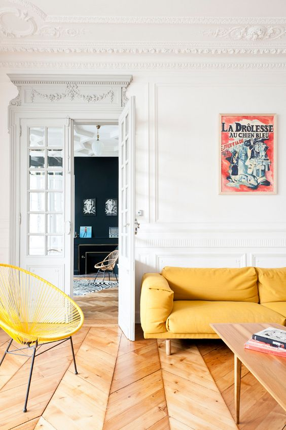 a refined Parisian living room with a yellow sofa and achair, a low table and a vintage poster on the wall