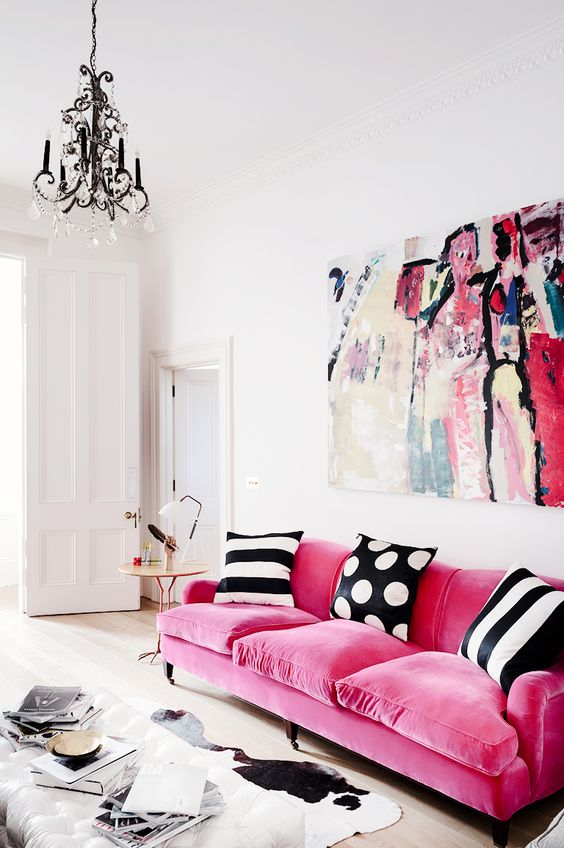 a refined contemporary living room with a hot pink sofa with printed pillows, a bold artwork, a crystal chandelier and a white ottoman