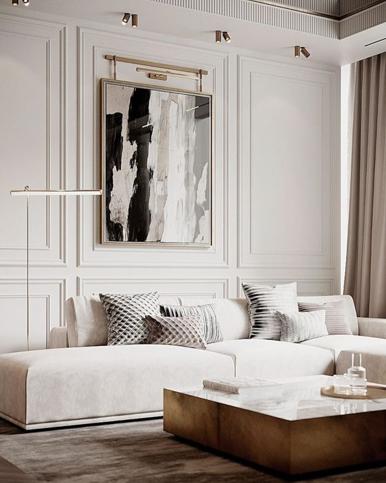 a refined contemporary living room with a low creamy sofa, a low table, a statement artwork and some lamps and lights