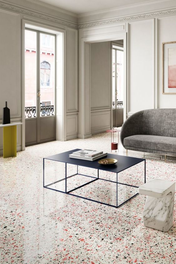 a refined contemporary living room with colorful terrazzo floors, bold and scu;ptural furniture and lovely paneling