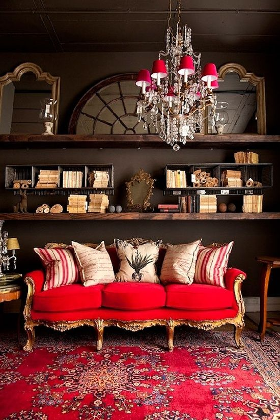 a refined eclectic living room with dark walls, dark stained shelves, a refined gold and red sofa and a catchy chandelier