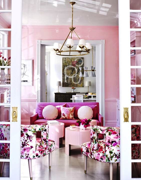 a refined feminine living room with pink walls, a pink loveseat, floral chairs, blush coffee tables and pillows and a chic chandelier