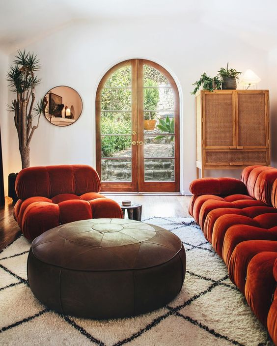 a refined living room in neutrals, with a burnt orange sofa and a chair, a round leather ottoman, a rattan sideboard